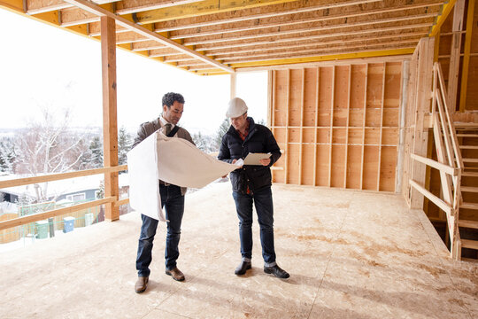 Homebuilder and architect with blueprints at home construction site