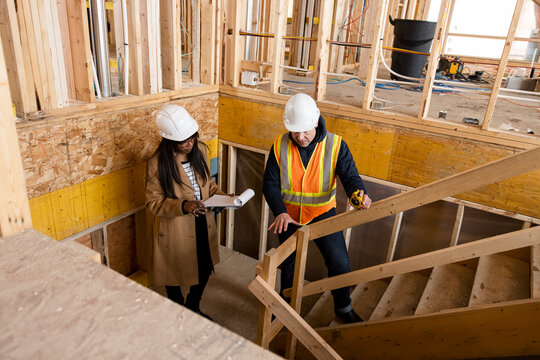 Homebuilders with clipboard inspecting framing at construction site