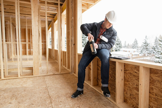 Male homebuilder with coffee thermos at home construction site
