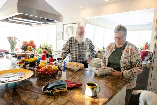 Couple preparing eggs in kitchen