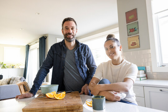 POV portrait happy couple eating oranges and video chatting in kitchen