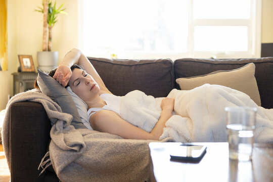 Sick woman sleeping on living room sofa