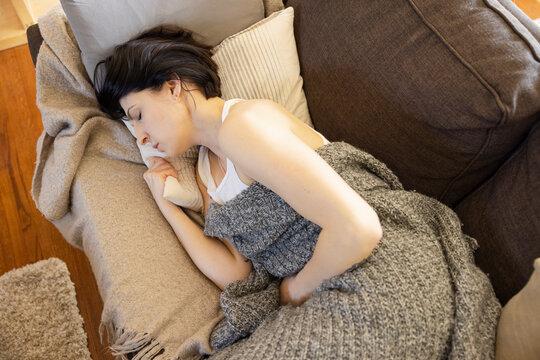 Sick woman sleeping with blanket on living room sofa
