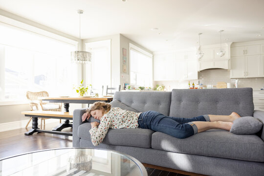 Exhausted woman napping on living room sofa