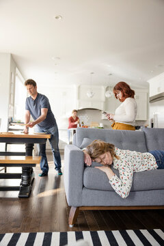 Tired woman sleeping on sofa while family prepares dinner in kitchen
