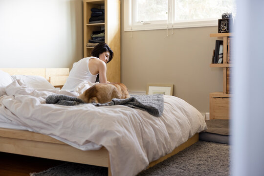 Woman with dog in morning bedroom
