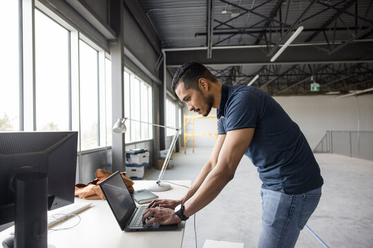 Man working on laptop in empty office space