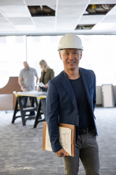 Architect in hardhat with clients in empty office