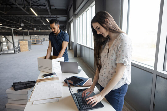 Woman working on laptop in empty office space