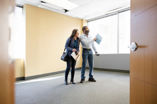 Realtor and client viewing empty office