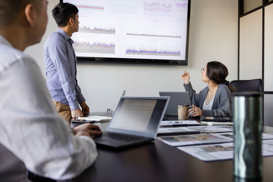 Business people reviewing data on screen in conference room meeting