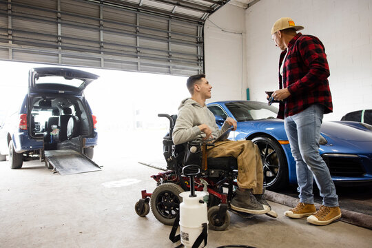 Disabled male worker talking with coworker in auto body shop