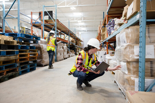 Male worker in protective workwear with laptop in warehouse