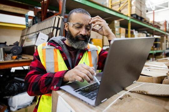 Focused male warehouse worker using laptop