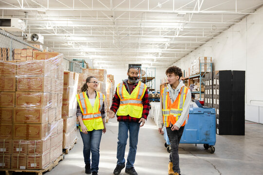 Warehouse workers in reflective vests talking and walking