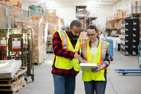 Warehouse workers with clipboard talking