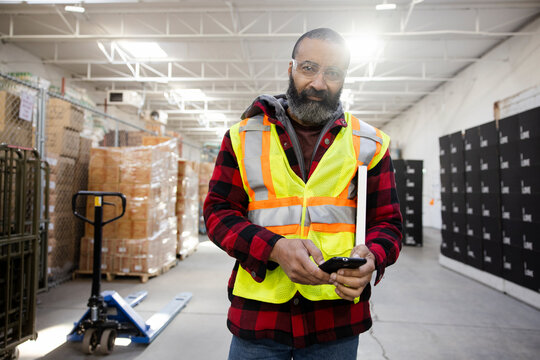 Portrait male warehouse worker in reflective vest using smart phone