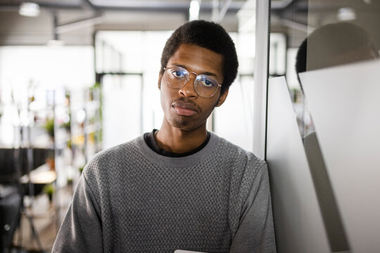 Portrait confident young businessman in eyeglasses in office