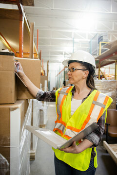 Female warehouse worker checking inventory