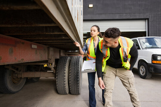 Warehouse workers with clipboard inspecting delivery truck