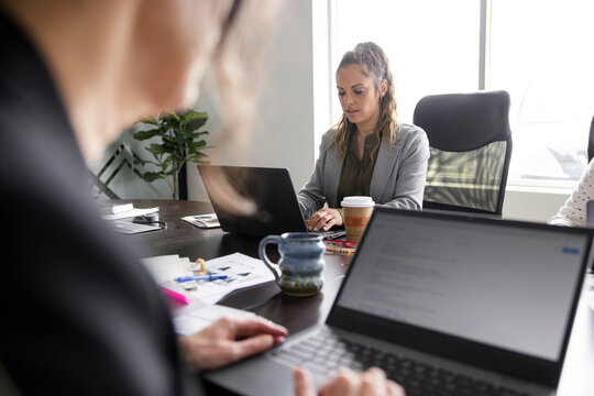 Businesswoman working at laptop in conference room meeting