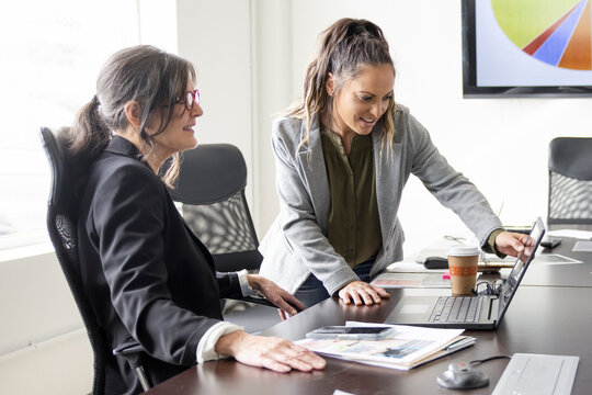 Businesswomen talking at laptop in conference room meeting