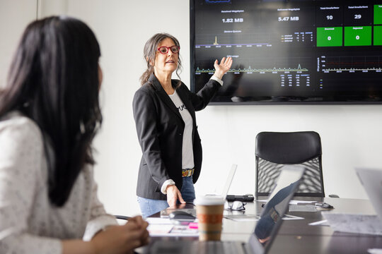 Businesswoman leading meeting at screen in conference room meeting