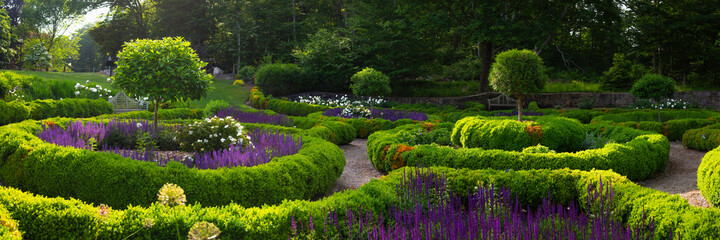 Courtyard French Style Garden Landscape. Classic Style Cultivated Homestead Plants and Flower Bed Design. Panoramic Backdrop Image with Space for Text or Design.
