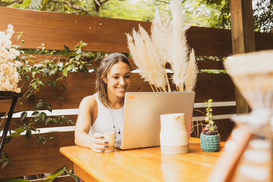 Beautiful freelancer smiling working on laptop with coffee cup in an artisanal coffee shop. Plumes and plants being seen through wood planks wall gaps in the background.
