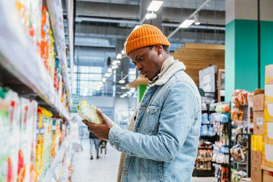 Thoughtful African-American man chooses juice in paper pack standing near large rack in modern supermarket department side view
