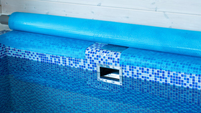 Blue tarpaulin pool cover. Bubble awning wrap for swimming pool cover. Swimming pool with a blue water.