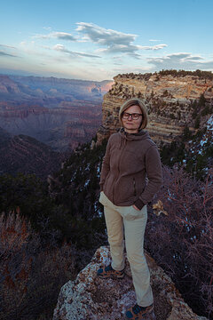 a woamn standing on a cliff over the valley of Grand Canyon during a sunset