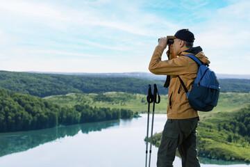 Obraz Hiker man looking in binoculars on the mountain. Hiking active people lifestyle. - fototapety do salonu