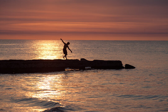 Backlit silhouette of cheerful person on rocks on the beach un cuba