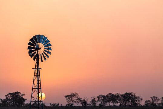 Windmill against a smoky sunset in drought conditions