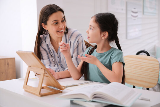Mother helping her daughter doing homework with tablet at home