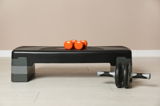 Step platform, dumbbells and abdominal wheel indoors. Sports equipment