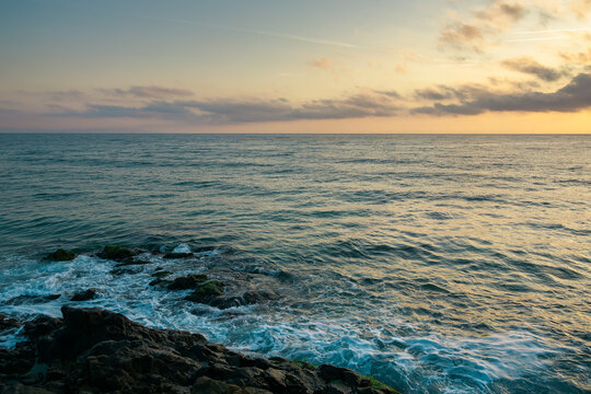 landscape at the sea. beautiful nature background in autumn at sunrise. clouds on the sky above horizon in morning light. water waves crashing coastline. sunny weather. travel in velvet season