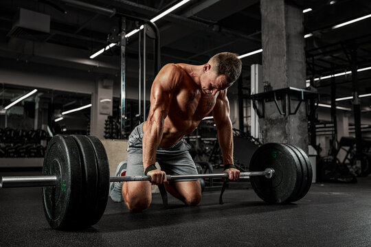 The concept of motivation, overcoming yourself and your fears, an athlete in the gym doing exercises with a barbell.