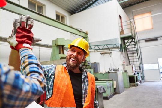 Handwerker begrüßt einen Kollegen mit High Five