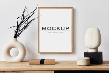 Obraz Stylish interior of living room with mock up poster frame, wooden commode, book, black leaf in ceramic vase and elegant personal accessories. Minimalist concept of home decor. Template. - fototapety do salonu