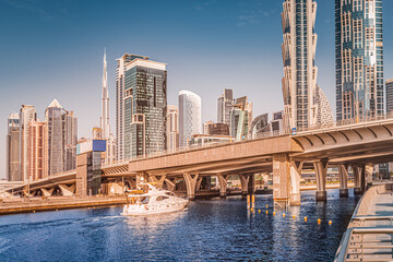 Fototapeta Luxury speedboat sails under the bridge in Dubai Downtown Center with stunning views of numerous skyscrapers and hotels obraz