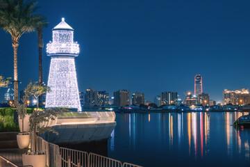 Fototapeta Illuminated decorative lighthouse near the parking lot of yachts and ships in the Dubai Creek Marina Harbor. Travel and tourist destinations obraz
