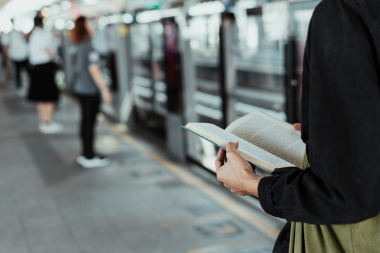 Midsection Of Woman Reading Book On Subway Station