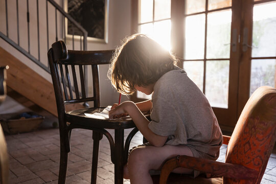 young boy writing on small chair at sunset