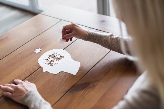 Blurred woman folding jigsaw on wooden table
