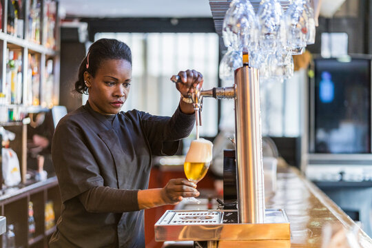 Ethnic bartender pouring beer in glass
