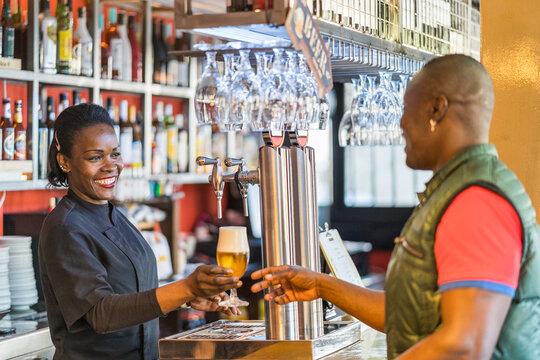 Ethnic bartender serving beer for customer in bar
