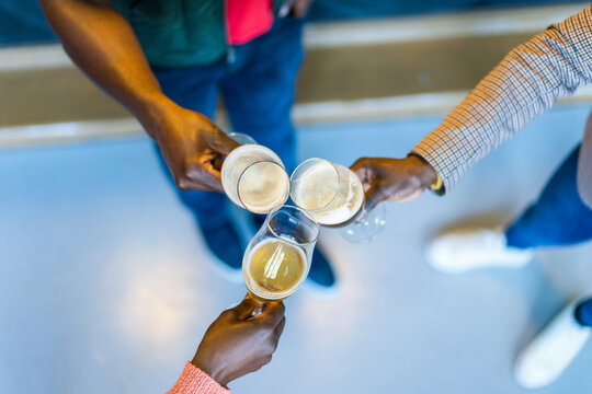 Anonymous black friends drinking beer in bar
