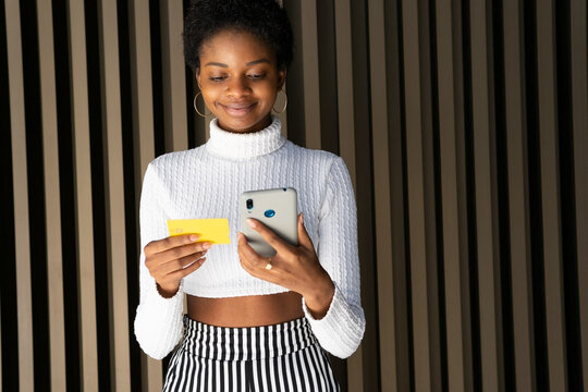 Glad black woman making online purchases on street